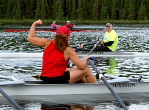 Photos by Jenny Neyman, Redoubt Reporter. Nancy Saylor salutes Tiger Demers, in yellow, during a practice of the Alaska Midnight Sun Rowing Association on Mackey Lake in Soldotna on Saturday. Saylor, Demers and Judy Demers, at center in pink, are among nine local rowers heading to Italy to participate in international rowing competitions.