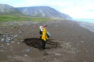 McKittrick stands next to a sinkhole in a beach on the Chukchi Sea, evidence that permafrost deep below is melting.