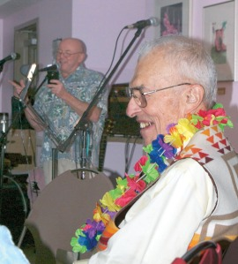 Photos by Jenny Neyman, Redoubt Reporter. Mike Morgan offers a happy birthday wish to Jim Fisher on Aug. 28 at the Kenai Peninsula Food Bank. Fisher, known for attending just about every music event in the central Kenai Peninsula, had the area's musicians show up to serenade him for his 86th birthday.