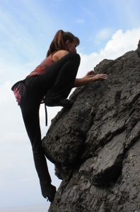 Natalie Larson climbs The Seed of Redoubt, a conglomerate rock boulder pitted like lava rock. Leg flexibility provides an advantage when footholds are hard to reach.