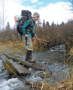 Grace navigates a stream crossing, carrying her own weight in gear and food in her pack.