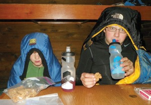 Grace and Billy warm up in their sleeping bags in one of the many public-use cabins available to rent along Resurrection Pass Trail.