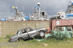 Old vehicles rest before the tops of the favored mode of transportation in Dillingham — boats.
