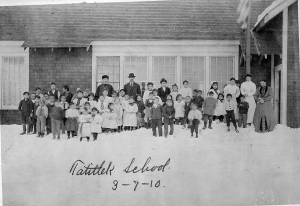Students and staff of Tatitlek School are pictured in March 1910. The teacher, pictured at center, is likely Arch R. Law, the first teacher at the American Territorial School in Kenai. Law only taught in Kenai the first year the school was in operation, in 1909, before moving on.