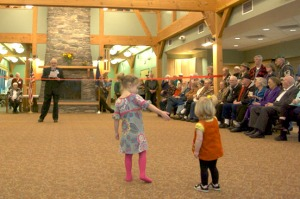 Photos by Jenny Neyman, Redoubt Reporter. Kylia, 4, and Eileen, 21 months, are among the many listeners to a presentation by Jesse Lobdell. president of the Nikiski Senior Center Board of Directors, at a ribbon-cutting ceremony at the new center on Saturday.