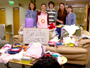 Photo by Jenny Neyman, Redoubt Reporter. Volunteers of Sarah's Closet display some of the donations of baby clothes they've gathered at the maternity department at Central Peninsula Hospital. Each new baby at CPH will be sent home with an outfit, blanket and other gifts, in memory of nurse Sarah Slegers, who died of cancer in July. From left are Julie McElroy, Stephanie Ferguson, Ian Ferguson, Molly Noyes and Karena Jenkins.