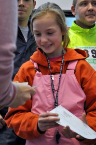 Photo by Joseph Robertia, Redoubt Reporter. Emma Mullet accepts a donation during a five-kilometer walk/run held in Kenai on Saturday as a fundrasier for St. Jude Children's Research Hospital