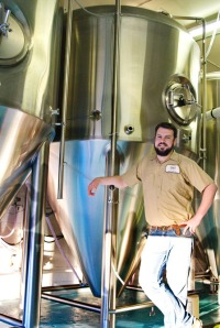 Photo courtesy of Elaine Howell. Devin Wagner, new brewer at Kenai River Brewing Co., stands with the brewery's new fermenter.