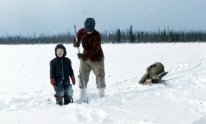 Clark Fair and his dad, Calvin Fair ready an ice-fishing hole in 1962.
