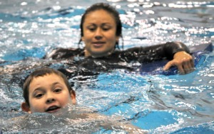 Photos by Joseph Robertia, Redoubt Reporter. Special Olympics athlete Bryce Braun is all smiles while taking part in a swimming practice for the Central Peninsula Special Olympics Team at Skyview High School in April. He is aided by Alanna Hutto.