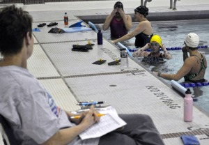 Master swim club coach Joanne Wainwright provides instructions to several swimmers during a weekly session.