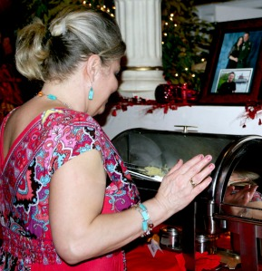 Adele Bearup checks the pasta she made for the veterans' Valentine's Day dinner Friday. Above the buffet is a photo of her son, James, and his wife, Fawn.