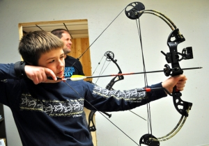 Photo by Joseph Robertia, Redoubt Reporter. Jaron Swanson, 12, takes aim at a target while his father, Aaron, watches his technique as they practice their archery Saturday at the range in the basement of Wilderness Way in Soldotna.