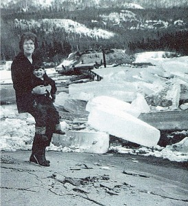 Photo courtesy of Mona Painter. Mona Painter holds her son, Peter Mlynarik (now the Soldotna chief of police) on top of the destroyed Kenai River bridge in Cooper Landing after the March 27, 1964, earthquake. Giant chunks of ice and other debris litter what used to be the community's access across the lake.