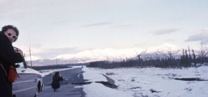 Photo courtesy of Kenai Peninsula College Photo Archive. Jean Brockel, of Soldotna, checks out damage to the Sterling Highway from the Good Friday quake on the flats east of Sterling. Also still noticeable are standing dead trees, a result of 1947 Kenai Burn.