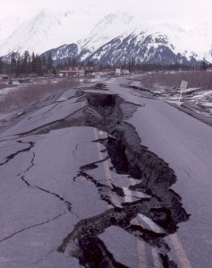 Photo courtesy of Kenai Peninsula College Photo Archive. A section of the Seward Highway on Turnagain Arm is destroyed after the 1964 Good Friday quake. In the background is the two-story Alaska Railroad depot at Portage, which was never reconstructed. Research following the quake opened the door to new information on the effects of soil liquefaction, the phenomenon to blame for much of the damage throughout Southcentral Alaska in the quake.