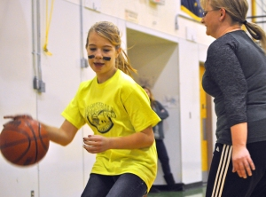 Photos by Joseph Robertia, Redoubt Reporter. Kilee Horning, a student at Tustumena Elementary School, pivots around teacher Lisa Gossett during the annual pre-spring break basketball game Thursday that pits faculty against the graduating class of sixth-graders.