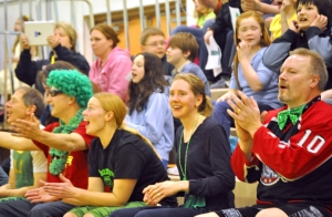 Faculty members and students cheer from the stands.