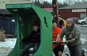 Competitors muscle their entry in the  outhouse race.