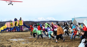 Photo by Clark Fair, for the Redoubt Reporter. A herd of kids scramble after candy and plastic balls dropped by a plane in the Beaver Roundup Festival in Dillingham on March 1.