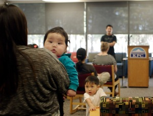 Kyree Sagoonick, 7 months, and her brother, Jaxon, almost 3, survey the room while Gabriel Stone shares his story.