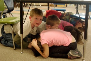 Kindergarten students at Soldotna Elementary huddle up under tables, cover their heads and remain still — well, mostly — during an earthquake drill Thursday at the school.
