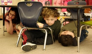 Photos by Jenny Neyman, Redoubt Reporter. Students in Jane Evenson's kindergarten class at Soldotna Elementary School practice staying safe during an earthquake drill held Thursday on the 50th anniversary of the 1964 Good Friday Earthquake in Alaska.