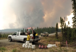 Tony Eskelin, in truck, left, and David Powell, both of Soldotna, help a Hotshot crew unload supplies in preparation for a controlled burn to extend a firebreak along Moose Ridge Avenue just south of Brown's Lake in Funny River on Saturday.  The Funny River Horse Trail Fire, approaching behind them, made a sudden jump toward the road on which they were working Saturday afternoon, necessitating a quick retreat.