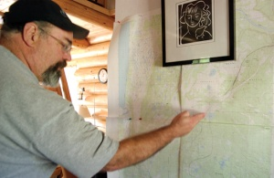 Mike Duhan marks the Funny River Horse Trail Fire's progress Saturday on a map set up on the wall of his home near Kasilof. He and his neighbors were under an evacuation alert over the weekend due to encroaching fire activity.