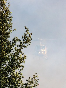 A Forestry helicopter emerges from the smoke after dropping a load of water on the perimeter of the fire. Two helicopters and two air tankers were put to use Monday and Tuesday, as well as 40 people fighting the fire on the ground.