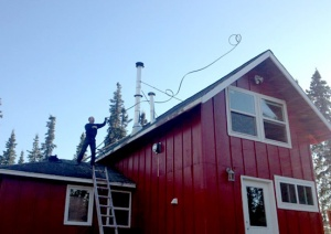 Photo courtesy of Jill Garnet. Sean Rice throws a soaker hose over the roof of his home in Kasilof in preparation of evacuation in advance of the Funny River Horse Trail Fire last week.
