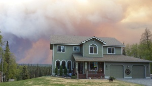 Photo courtesy of Stacy Schweigel. The Funny River Horse Trail Fire rages beyond Dan and Stacy Schweigel's home near Kasilof on Friday evening, prompting an evacuation alert for the area.