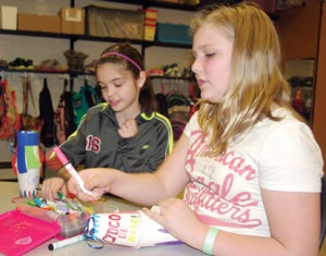 Redoubt fifth-graders Erica Arthur and Taylor Edwards label their pinatas with Cinco de Mayo, commemorating the Mexican holiday as well as the final visit from SoHi Spanish students for the year.