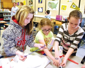 Redoubt Elementary fifth-graders (from left) Hailey Blischke, Alexis Gomes and Catie Kline work on their Cinco de Mayo project during a visit from Soldotna High School Spanish students.