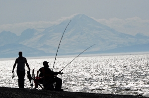 Photos by Joseph Robertia, Redoubt Reporter. An angler carries a halibut, caught from shore near the mouth of the Kasilof River recently, while his friend continues to monitor his line from a camp chair. The from-shore fishery is becoming a popular way to try for halibut.