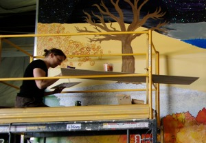 Photo by Jenny Neyman, Redoubt Reporter. Heather Floyd works on a portion of the Paint the Kenai mural last month.