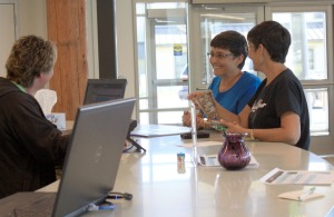 Karen Tollackson, left back, and Sharon Isaak, front right, chat at the center's reception desk as Isaak explains how she made a birch-bark basket she recently completed in a wellness activity arts and crafts class held at the center.