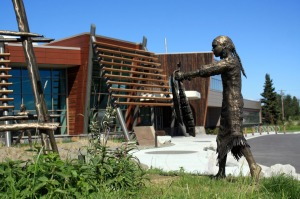 "Photos by Patrice Kohl, for the Redoubt Reporter. A ""Łuq'a Nagh Ghilghuzht"" sculpture by Joel Isaak depicts traditional Dena'ina life at fish camp outside the Kenaitze Indian Tribe's new Dena'ina Wellness Center in Old Town Kenai."