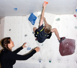 Natalie Larson guides David Schramm through an advanced maneuver — grabbing holds above one's head. Natalie and husband, Nic, built a climbing wall in their garage that can be customized to offer many levels of challenge.