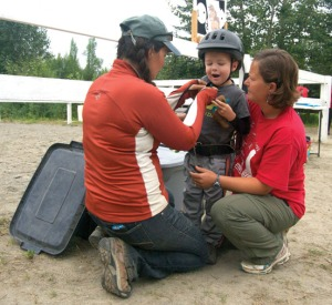 Therapists Noelle Miller, left, and Angela Beplat prepare Finn Wight for a hippotherapy session last summer in Sterling. Nature's Way moved its program to a new riding arena off Kalifornsky Beach Road this summer, which means less of a workload for the providers who were having to trailer and haul the therapy horses each day.