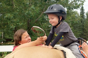 """Beplat, an occupational therapist, works with Finn Wight, getting him to interact with """"stop"""" and """"go"""" signs in order to make the horse move."""