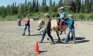 """AngelaBeplat, occupational therapist and founder of Nature's Way, directs Lachlan McManus to """"steer"""" the horse in his therapy session July 30. Hippotherapy utilizes the movements of horses to help achieve treatment goals."""