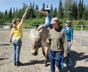 Photo by Jenny Neyman, Redoubt Reporter. Lachlan McManus captures a ring during an exercise in his hippotherapy session with Nature's Way Rehabilitation Service on July 30 in Kenai.