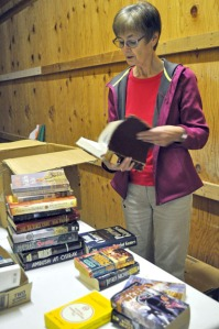 Photos by Joseph Robertia, Redoubt Reporter. Kathy Heus, chair of the Friends of the Kenai Community Library's annual book sale, sorts books at the Home Gallery in Kenai in preparation for the event.