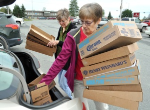 Volunteers Carolyn Ostrander and Kathy Heus unload boxes from the trunk of Heus' car. The boxes will be filled with books to make them easier to lift on to tables for the sale.