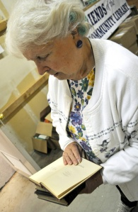 Volunteer Jean Taylor looks at a book published in the late 1800s. She said that some old books that show up in the sale can be quite valuable.