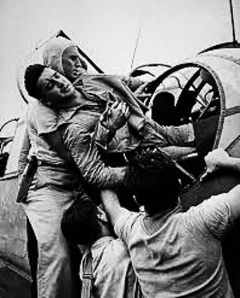 Illustration 5 — Wounded crewman assisted out of an aircraft.