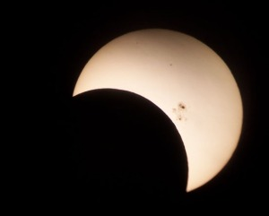 The edge of the moon is visible passing across the sun in the partial solar eclipse Oct. 23.