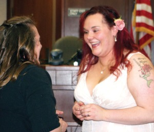 King laughs as she and Luck  finish exchanging rings during their wedding ceremony Friday.