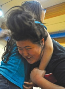 Photos by Joseph Robertia, Redoubt Reporter. Caitlin Sturman, of Kenai, tries to get out of a headlock imposed by her sister, Carly Sturman, during a free self-defense class for women put on last week by the Sterling Judo Club.